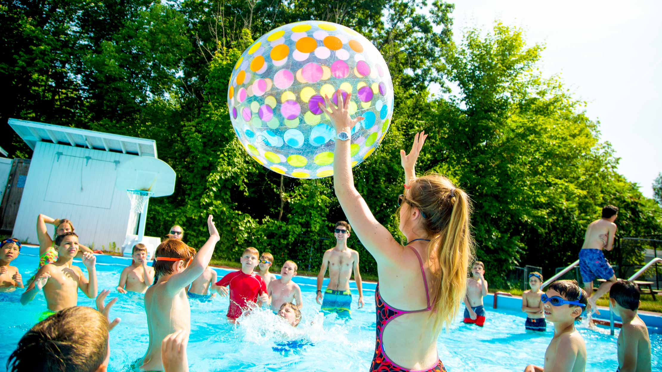 Campers play with inflatable ball in swimming pool