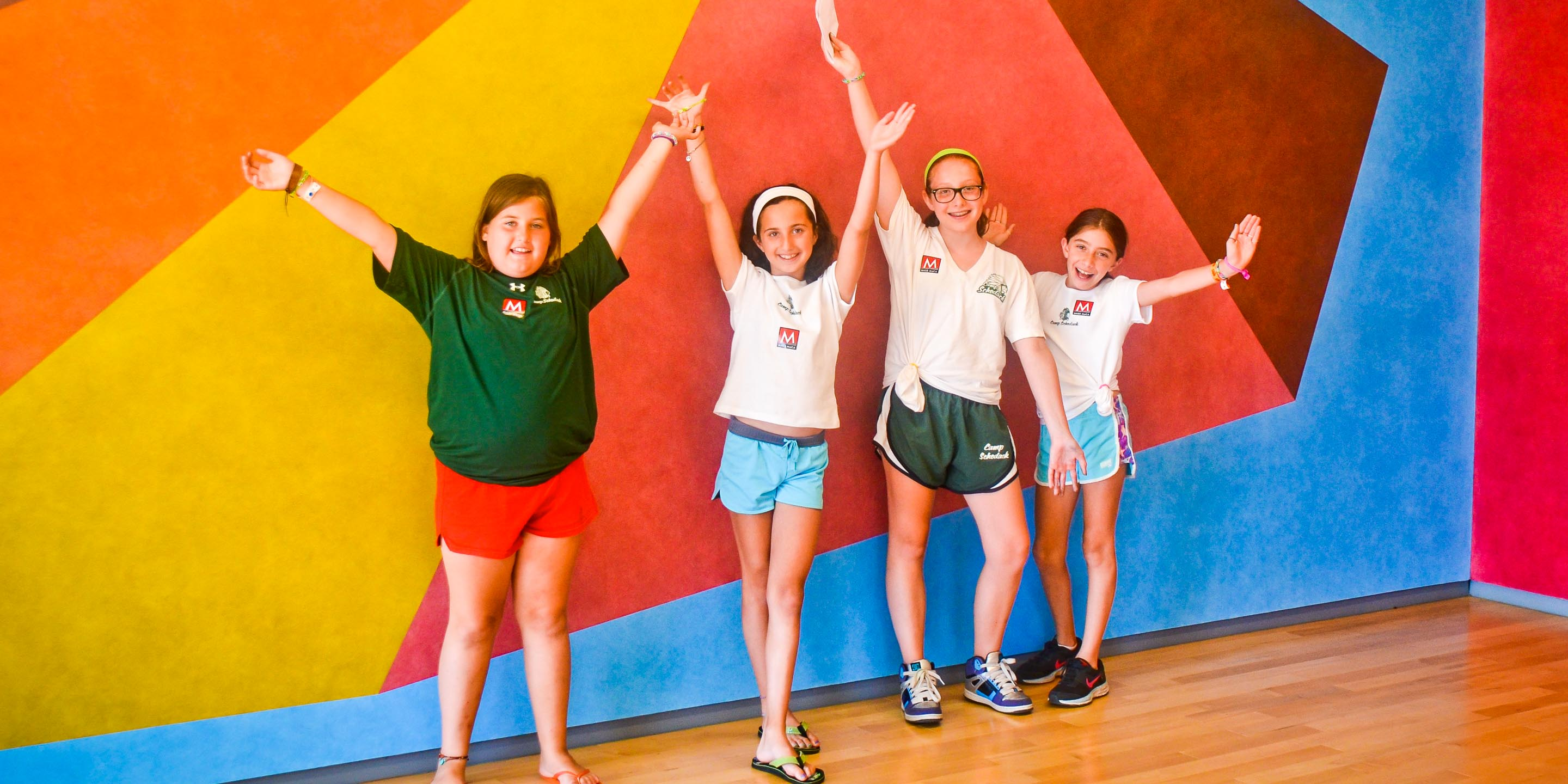 Girls pose in front of colorful wall during camp field trip