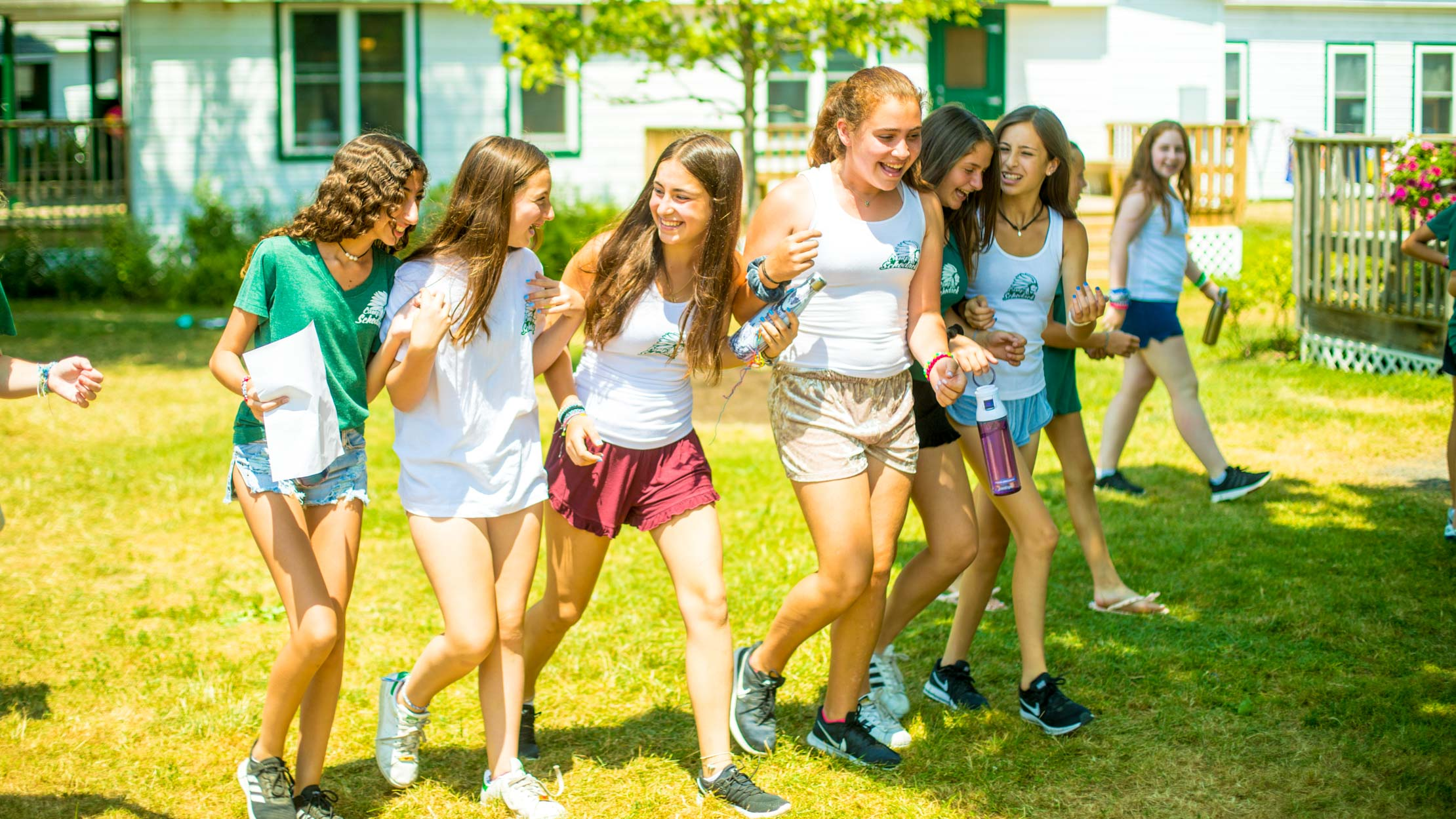 Girls laugh while walking across summer camp lawn