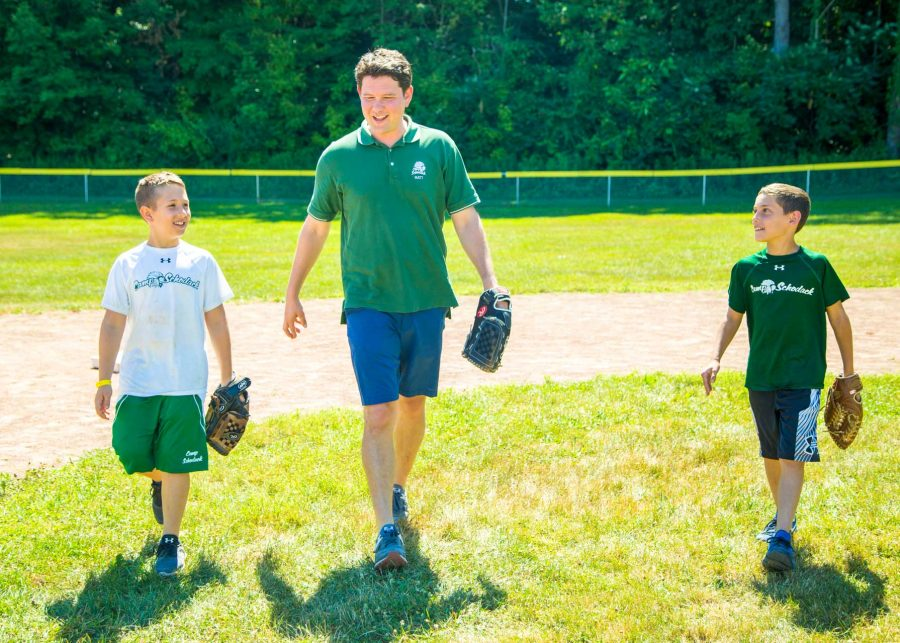 Matt walks beside campers on camp baseball field