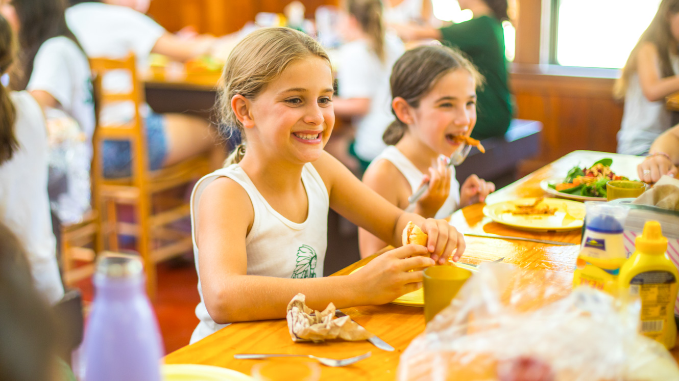Camper smiles while eating lunch in dining hall