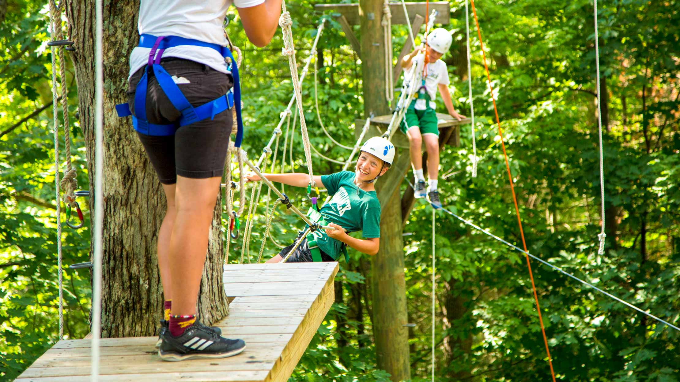 Smiling camper hangs on high ropes course