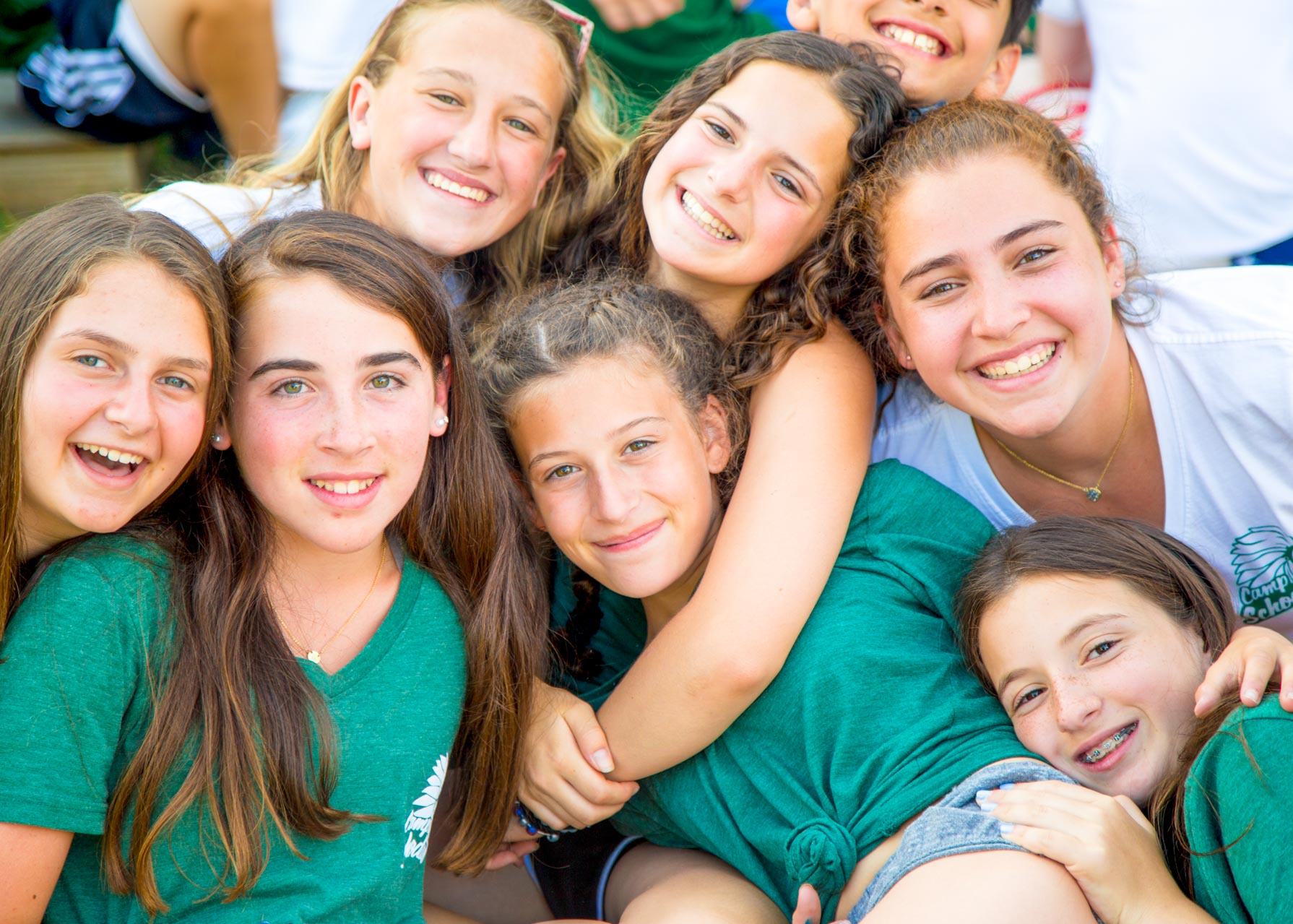 A group of smiling girls hug each other at summer camp