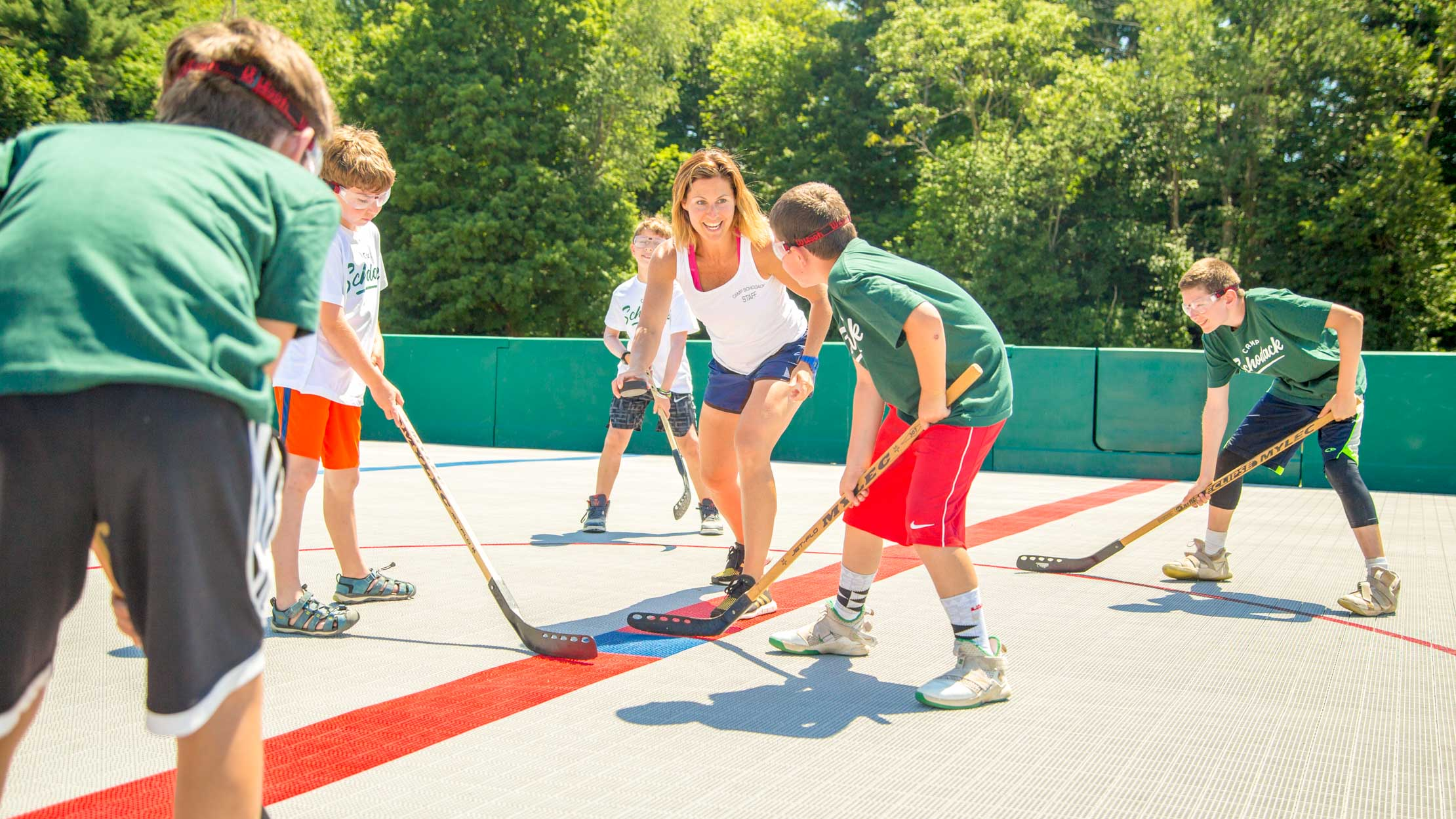Staff member preps campers for street hockey game
