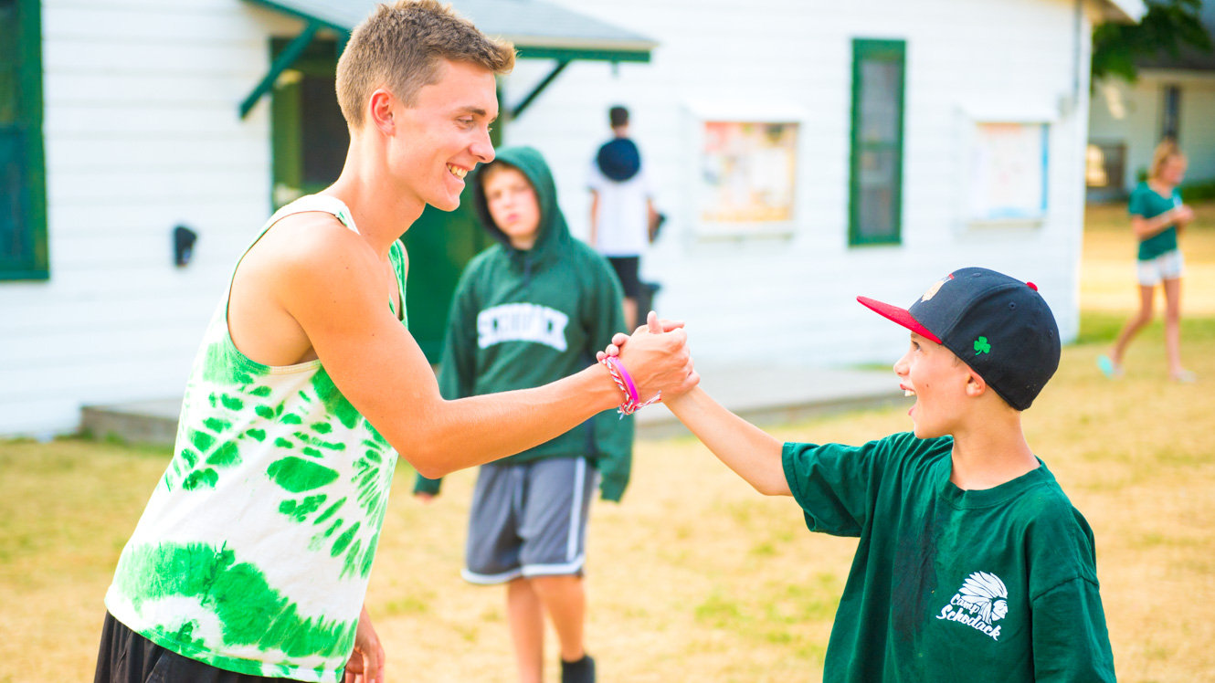 Counselor shakes hands with camper